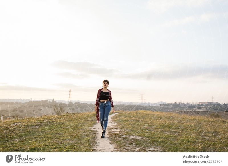 Female hipster in trendy outfit on empty rural road woman casual nature teen suburb field countryside grass sky lifestyle young cloudy walk meadow teenager rest