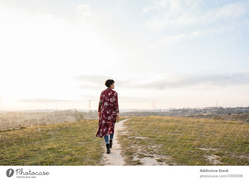 Anonymous female hipster in trendy outfit on empty rural road woman casual nature teen suburb field countryside grass sky lifestyle young cloudy walk meadow