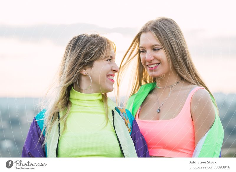 Cool modern females chatting on rural field women hipster teenager girlfriend colorful cool group wear attire rebel smile laugh enjoy talk conversation