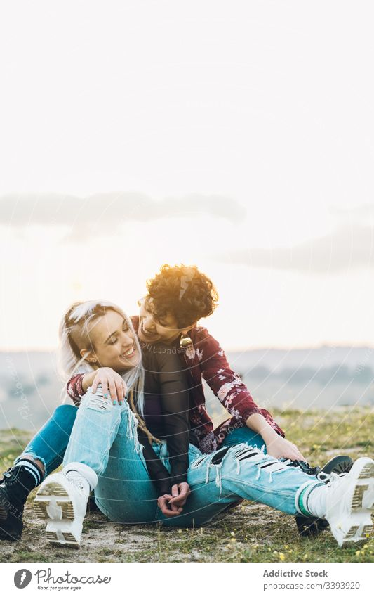 Content female teenagers hugging on grass women girlfriend laugh fun nature meadow best friend embrace smile enjoy share casual contemporary sit hipster green