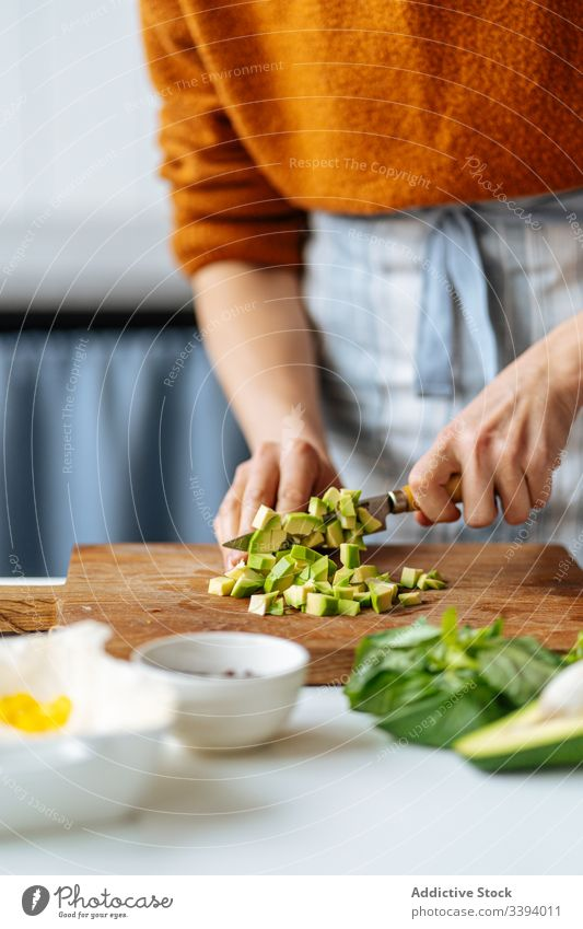 Woman cutting choppped avocado on cutting board food cooking recipe woman vegetable ingredient add healthy green kitchen meal female housewife dinner lunch home