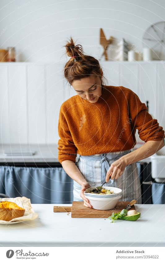 Woman adding raisins into bowl food cooking recipe woman ingredient vegetable healthy grain seed kitchen meal female housewife dinner lunch avocado home