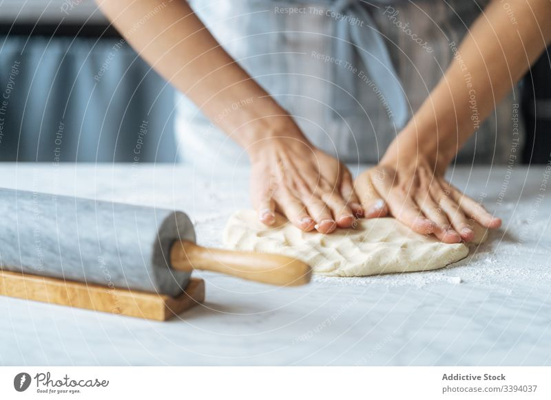 Cook kneading dough with hand on table cook rolling pin flour preparation bakery kitchen culinary making apron recipe food homemade prepare raw cuisine