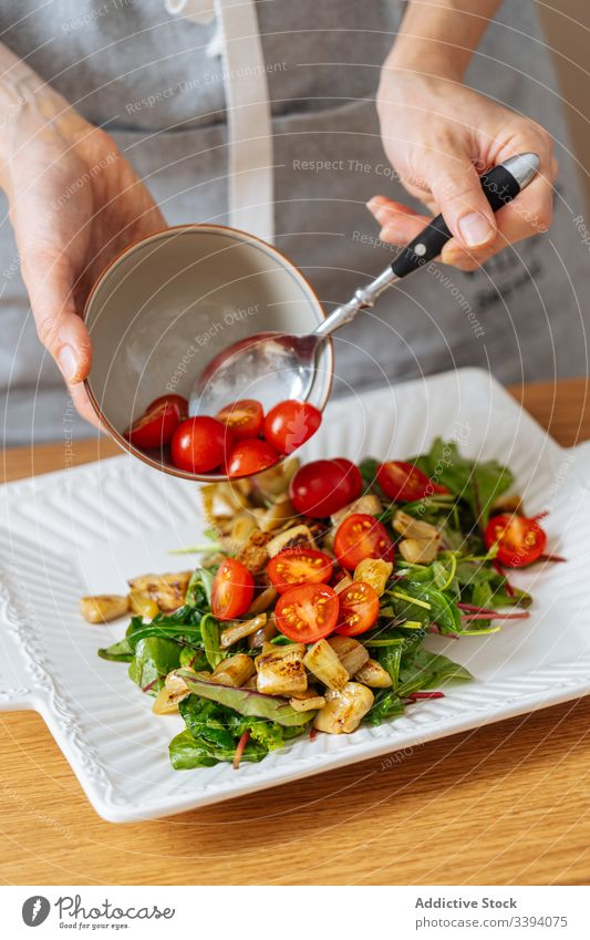 Woman putting tomatoes on salad food cooking woman cherry recipe vegetable ingredient kitchen healthy meal female housewife dinner lunch home preparation fresh