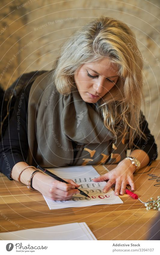 Female artist drawing with pencil in art studio woman lettering handwriting concentrate creative focus lifestyle study job sit sketch inspiration table paper