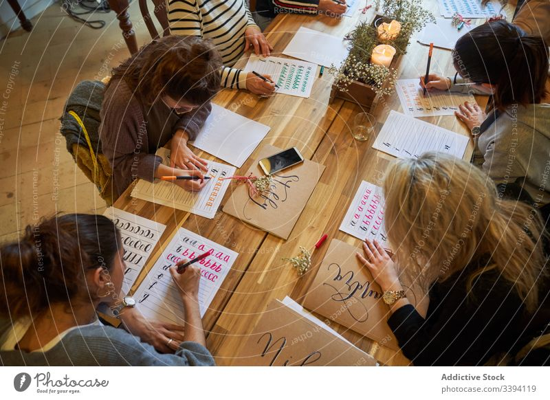 Lettering lesson in art studio draw students coach table group meeting casual lifestyle gather creative colleague cooperate collaborate interact project