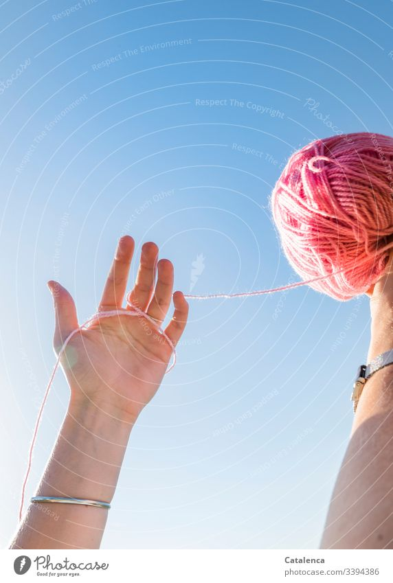 Hands holding a pink ball of wool against the sky hands Uphold Fingers Bangle Wool Ball of wool Sky Summer Blue Pink Crochet Warmth Leisure and hobbies Knit