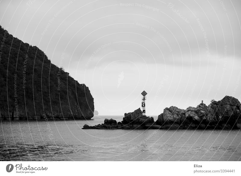 Rocks in the sea on which there is a little tower with a sign Ocean edged Landscape Halong bay Black & white photo fissured Tower Water Vietnam Nature Sky Gray