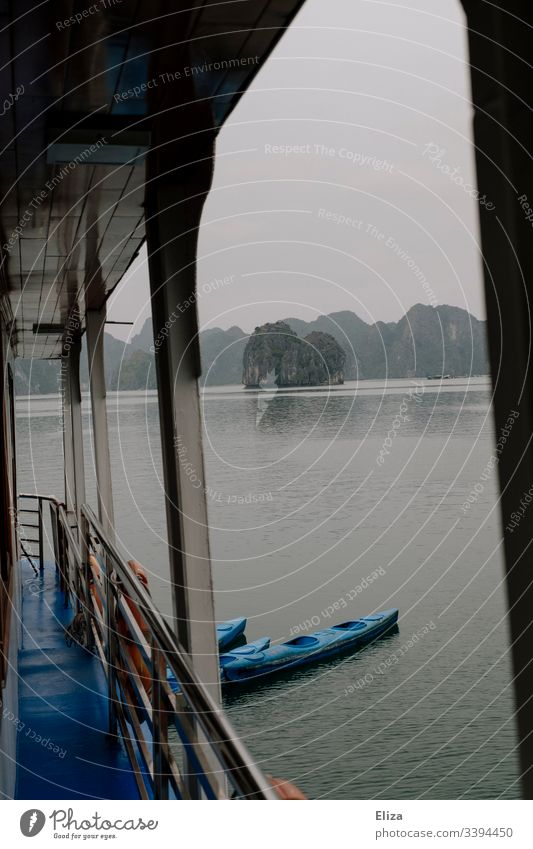View from an excursion boat, with railing and tethered kayaks, in Halong Bay in Vietnam; beautiful landscape with limestone cliffs rising out of the sea, in foggy weather