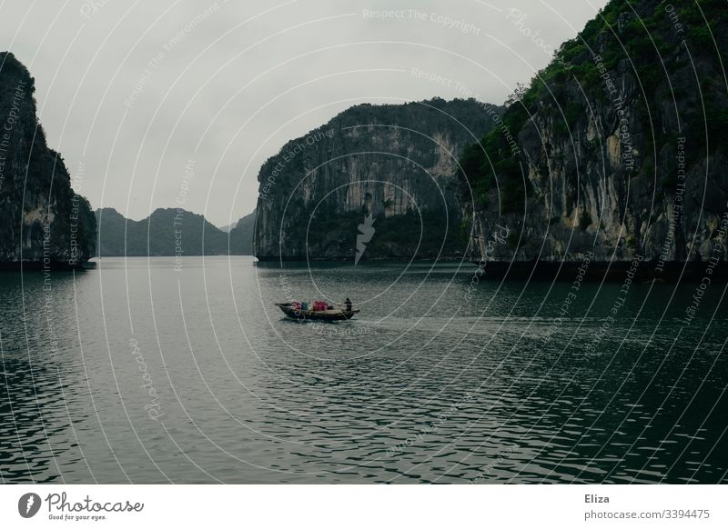 A fishing boat on the sea in Halong Bay in Vietnam; beautiful landscape with limestone rocks rising out of the sea in foggy weather Halong bay Ocean