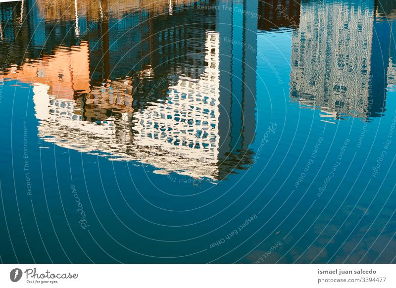 building reflected on the water in the river in Bilbao city Spain reflection light bright liquid sunlight blue abstract texture background pattern ripple wave