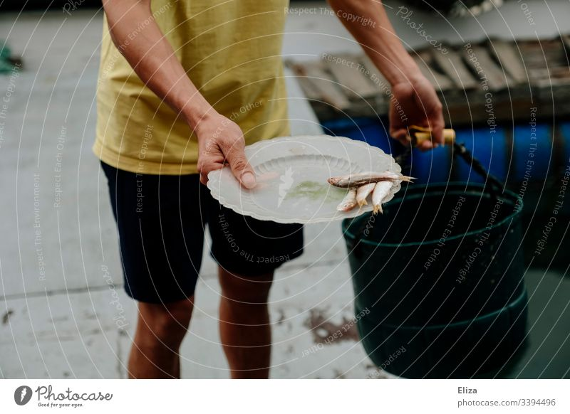A fisherman holds a plate with fish in his hand Fisherman fishing Fish breeding Feed Plate Man stop feed Water Fishery Documentary Vietnam Fishing (Angle) Catch