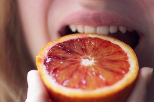 Woman bites into juicy orange Orange Fruit Macro (Extreme close-up) Nutrition Food Healthy Vegetarian diet Colour photo Organic produce Interior shot Diet