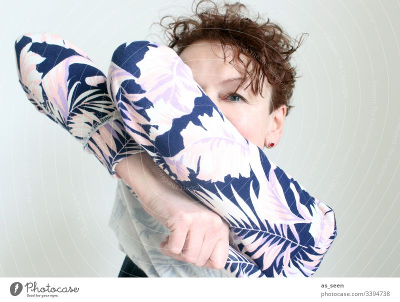Woman pulls a sweater over her head Sweater move out Looking Flowery pattern Colour photo Interior shot Feminine Adults Human being Looking into the camera