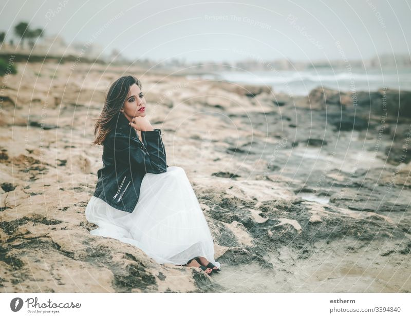 Pensive Young woman sitting on the beach young woman beautiful elegant elegance dream dreaming dreams dress fashion freedom fun glamor independence joy