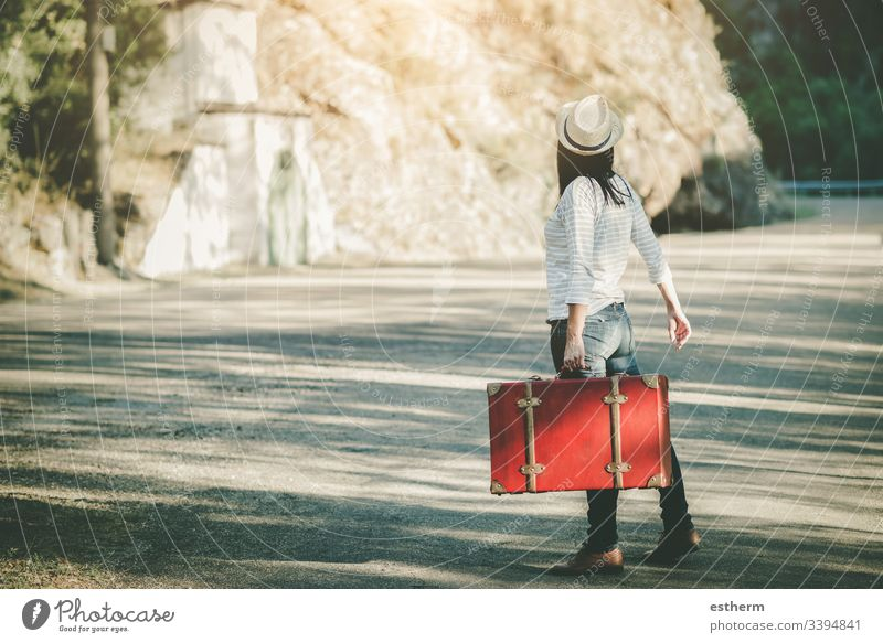 Young woman with suitcase on the road freedom fun girl happiness happy hat highway hitchhiker hope independence holidays adventure lifestyle motorway nature
