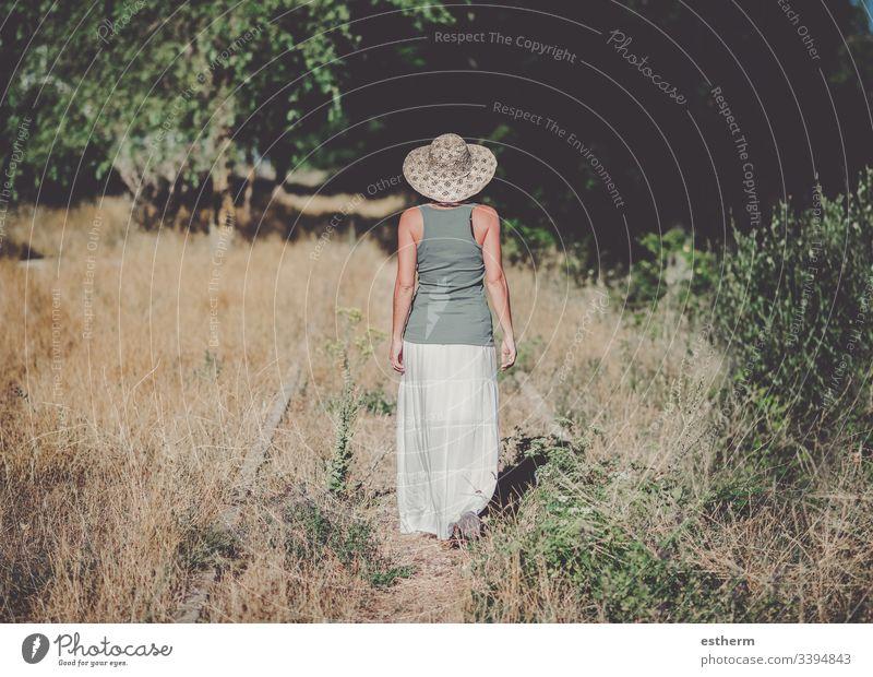 Back view of a Pensive Young Woman in the field young woman dreaming dreams freedom grass in love love landscape leisure lifestyle beautiful loneliness lonely