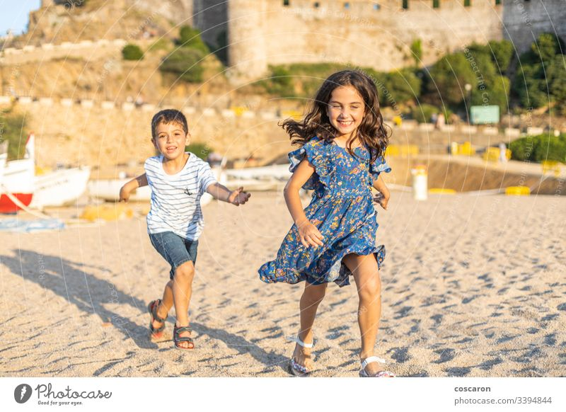 Two little friends running on the beach action active beautiful blue boys cheerful child childhood children colourful competition concept cute friendship fun