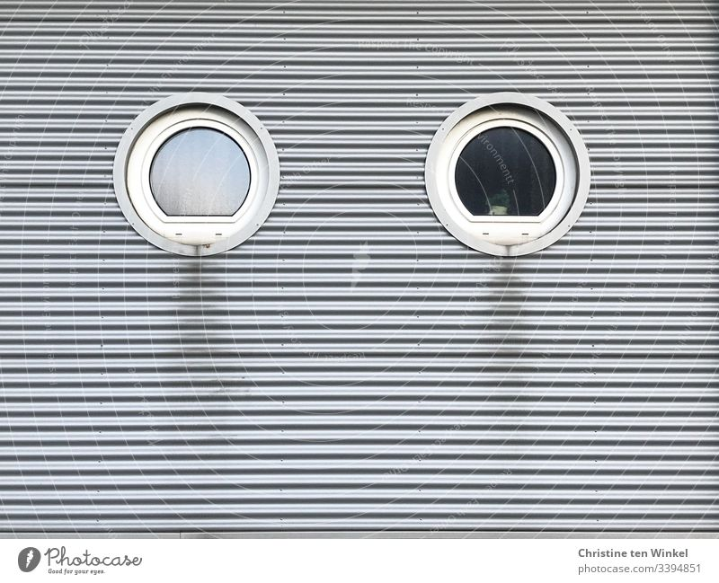 Two round windows in a clad house facade Window Round White Facade Building facade frowzy Silver Cladding silver Gray Gloomy Stripe lines Day Architecture built
