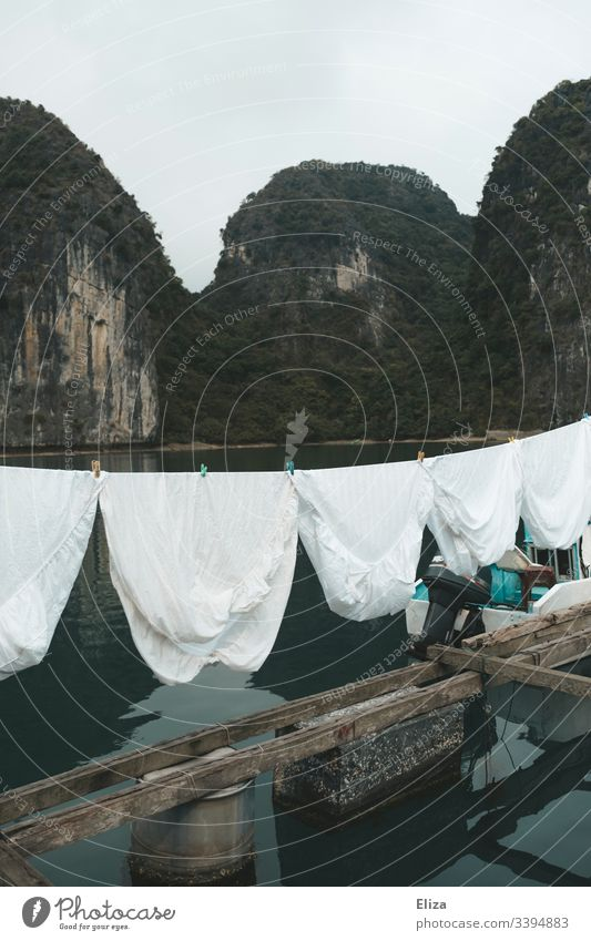 White laundry on a clothesline in a floating village in Halong Bay, Vietnam Clothesline Laundry Sheet Limestone rocks Landscape aquatic life wooden planks