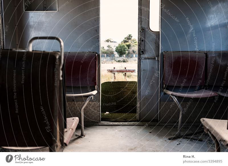Seats in a railway carriage with a view of the siding railcar Railroad vintage Deserted Retro Colour photo Detail dilapidated outlook seats Subdued colour