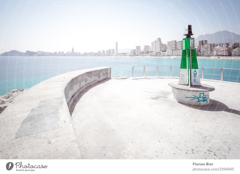 Lighthouse in the harbour with view of high-rise beach panorama over the sea Concrete Harbour Skyline Ocean High-rise graffiti dwell harbour bottom Beach Life