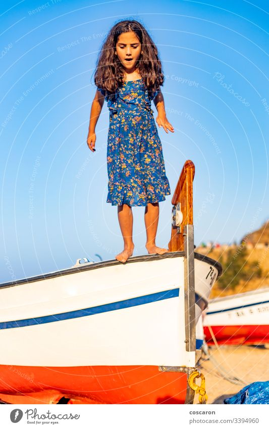 Little child jumping from a boat with a blue sky background active air beach beautiful boy carefree cheerful childhood coast coastline energy enjoy fly freedom