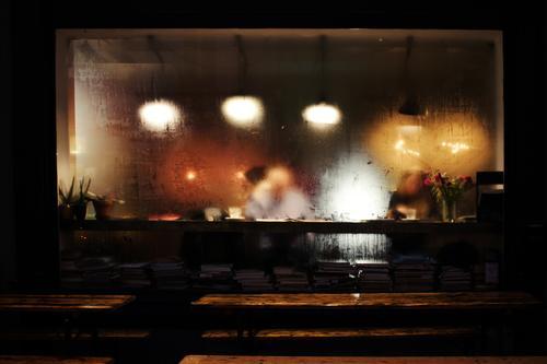 Anonymous Café Restaurant Lamplight Table Woman Man Reading Misted up Slice Window benches Pot plant flowers Quaint Cozy Rain raindrops clearer Colour photo