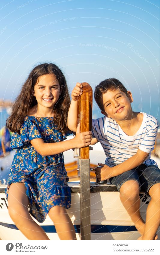 Portrait of two young children climbed in a fishing boat on the beach adventure blue board boy brothers captain childhood coast coastal cruise dress family