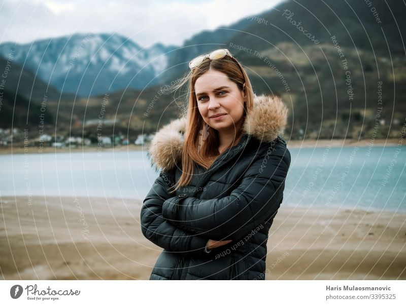 Young beautiful blonde woman in nature lakeside and mountain top in background adult adventure attractive beauty caucasian cold copy space cute dust face