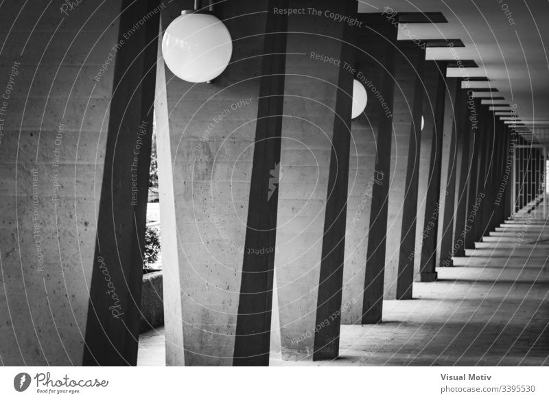 Outdoor hallway with columns in black and white grayscale photography greyscale contrast lamps outdoor exterior structure perspective abstract repetition