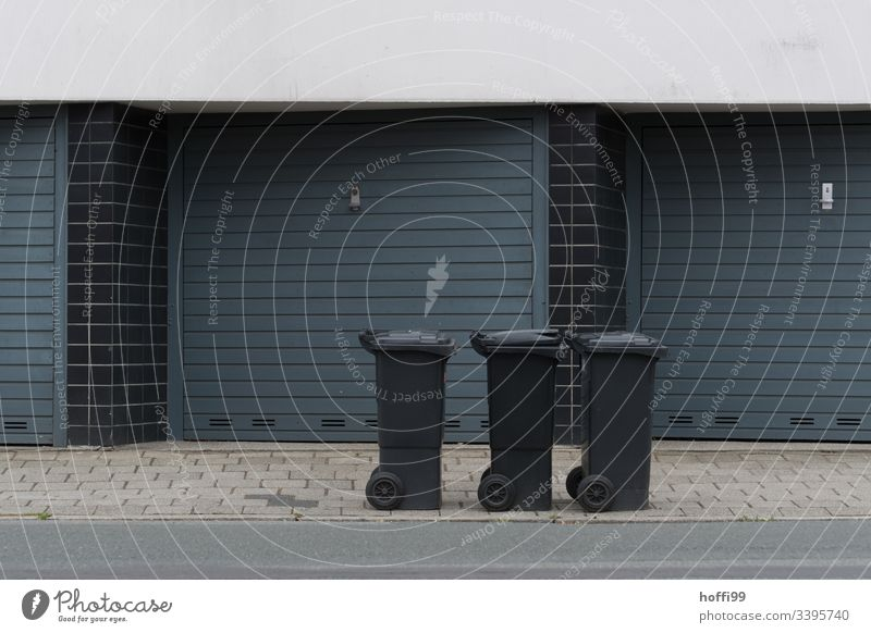three dustbins at the roadside Residual waste residual waste bin Refuse disposal Facade Garage door garage entrance Exterior shot Building