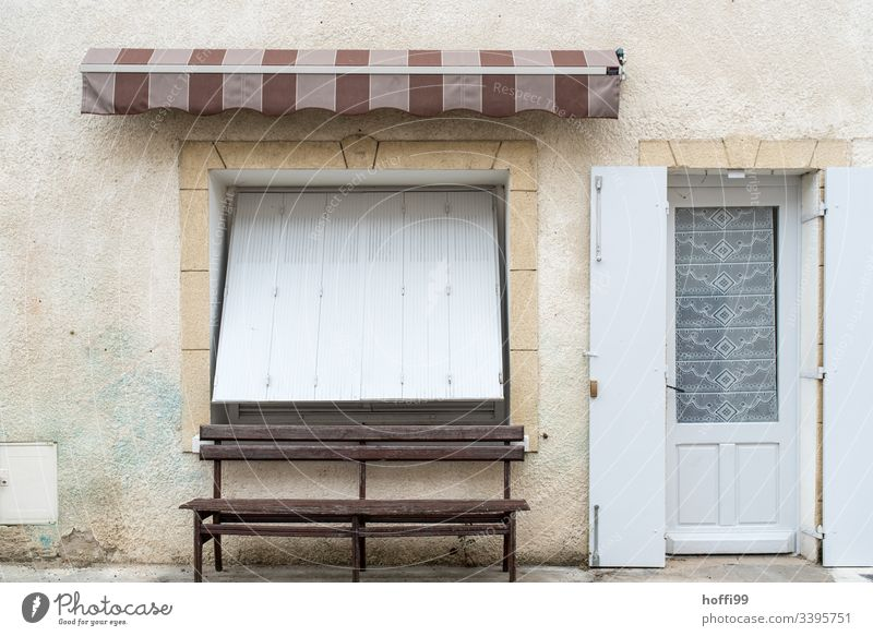 Still life of an old town facade with bench and closed shutter Old town Building Broken Wall (barrier) Roller shutter off Deserted Facade Architecture