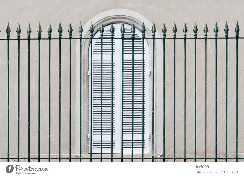 elegant high fence in front of windows with closed shutters Fence Arrow Window Shutter Lattice window Quarrystone facade Facade Wall (barrier) Wall (building)