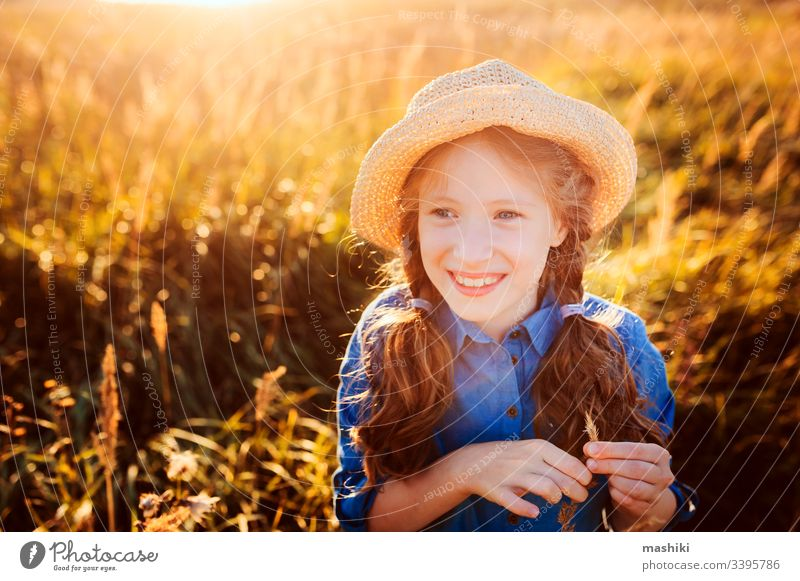 happy kid girl in blue dress and straw walking on summer sunny meadow. Lifestyle shot, rural living and summer traveling concept child nature lifestyle