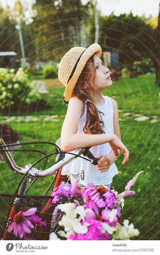 happy child girl in hat riding bicycle with bouquet of wild flowers, summer vacations concept book kid childhood outdoor nature park fun lifestyle read leisure