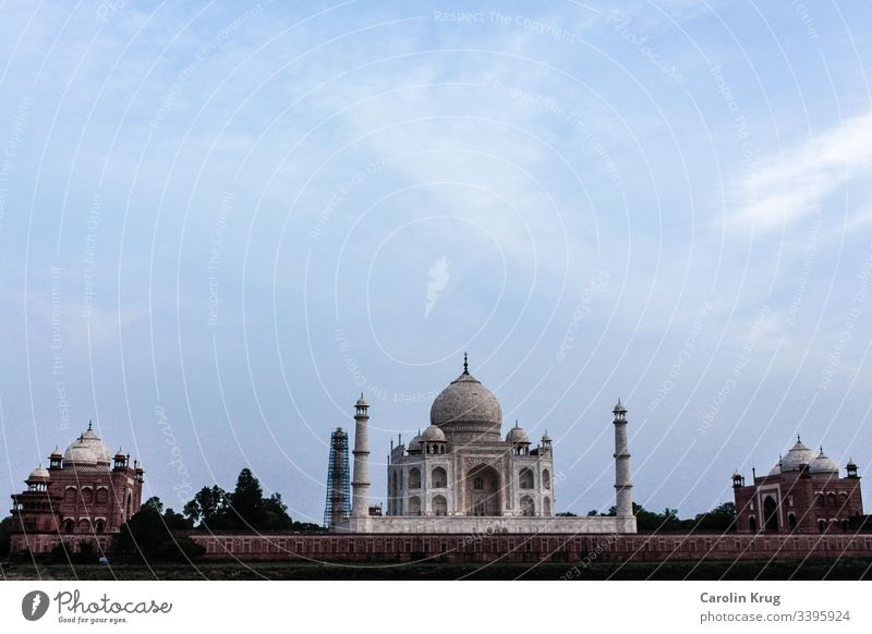 The fairytale Taj Mahal with its two outbuildings. Almost as if the two outbuildings made of sandstone guard the wonderful queen, the tomb of a great love.  A long shot from the other side of the holy Yamuna River