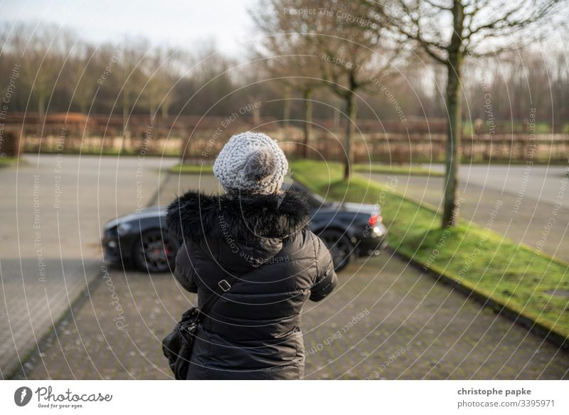Woman in black winter jacket and cap looking at black roadster on parking lot Jacket Black Motor vehicle Parking lot Day Sports car Car Exterior shot Vehicle