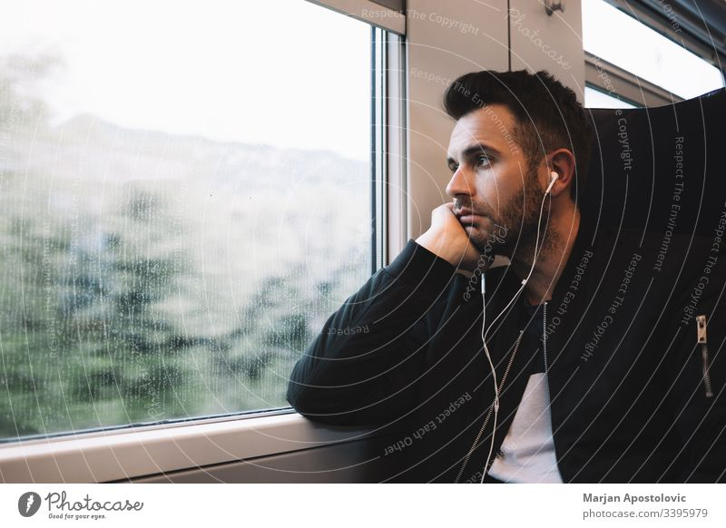 Young man traveling by train wearing earphones 30s adult alone bearded casual caucasian commute commuter day everyday guy handsome headphones journey life