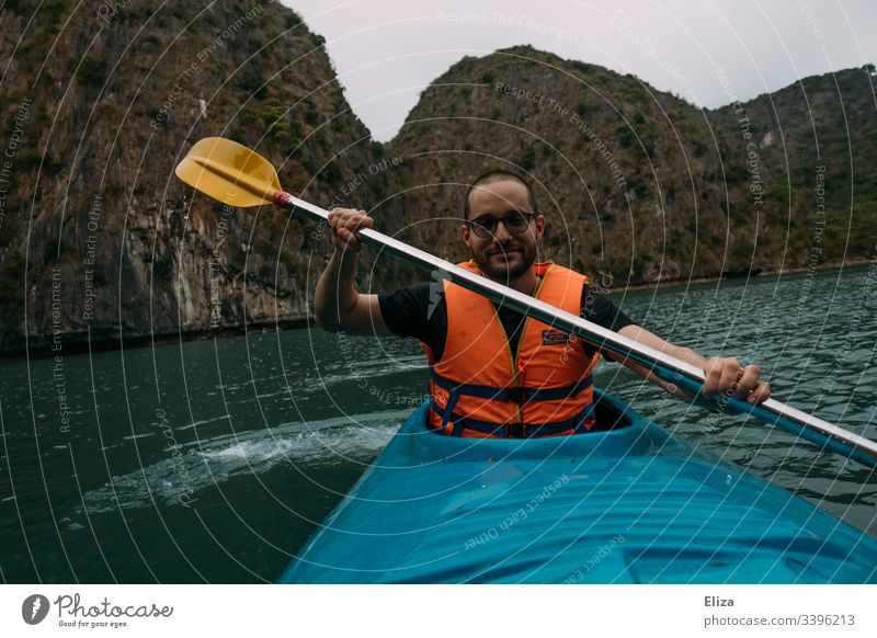 Man with life jacket kayaking in a blue kayak in Halong Bay, Vietnam Kayaks Sports Nature Landscape Halong bay Tourism Activity holiday fun Athletic Paddle Blue