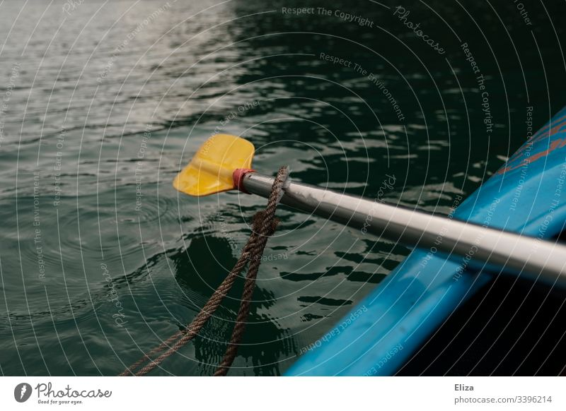 A yellow paddle sticking out of a blue kayak on the sea Paddle Kayak Ocean Sports Water Rowing Yellow Movement Exterior shot Vacation & Travel Aquatics