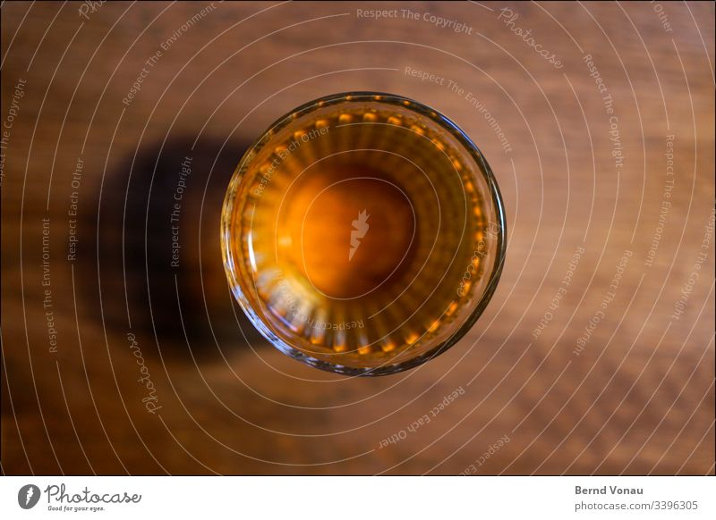 Drinking glass from above Glass Wooden table blurred edge at home Beverage drinking glass Close-up Fluid Alcoholic drinks Colour photo Yellow Artificial light
