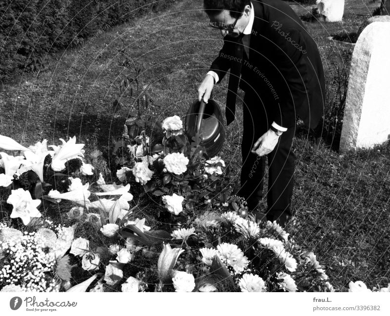 Something could still be done for the old man, he thought, and watered the flowers on the fresh grave. Grave Cemetery Grief Funeral Exterior shot Death Sadness