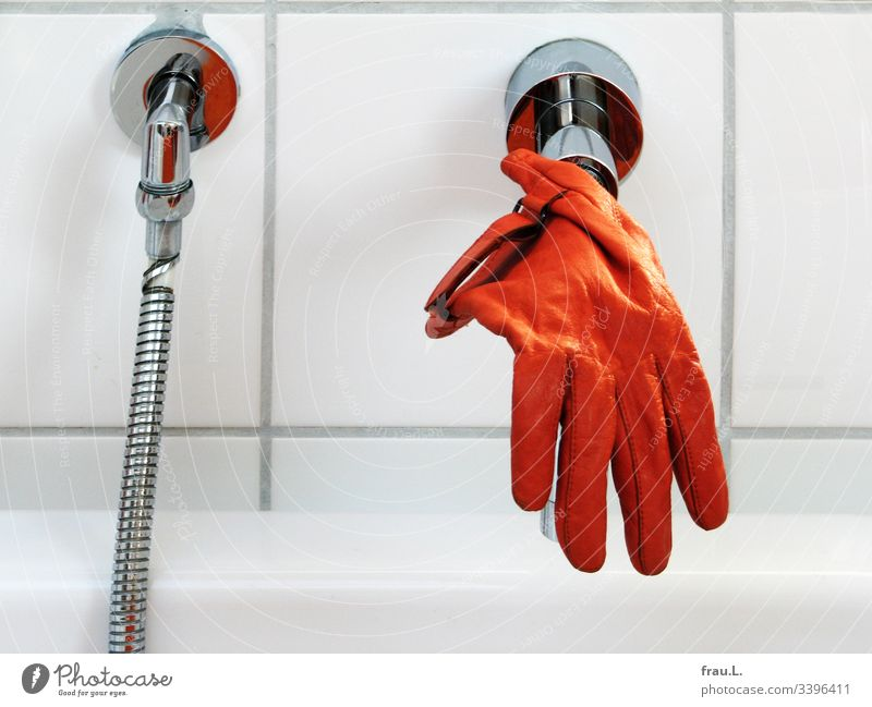 He couldn't remember how the orange glove had got on the tap, but he was now quite happy to dangle over the bathtub. Orange Bathtub Dry Clean Colour photo