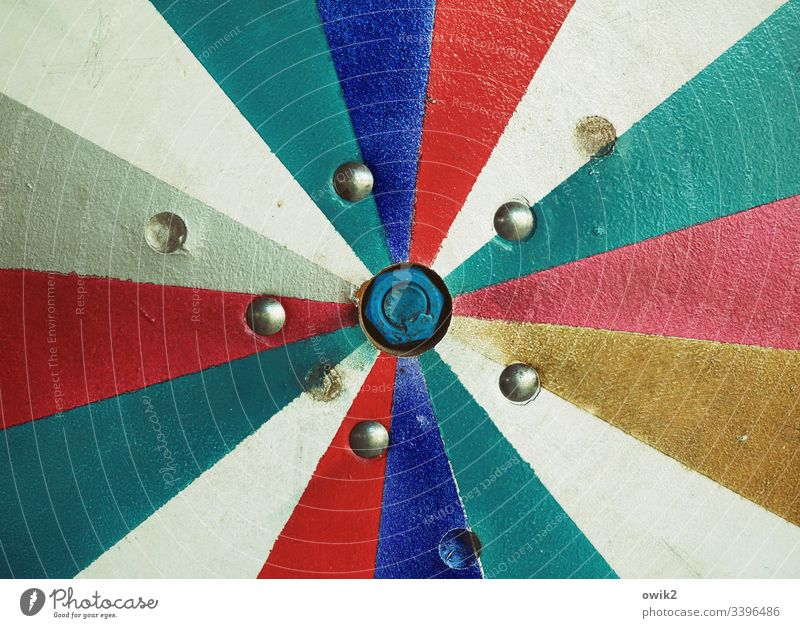 Big Bang wheel of fortune Middle Segments colors Centre red Turquoise Blue White Gold Screw center Colour photo Deserted Copy Space top Exterior shot