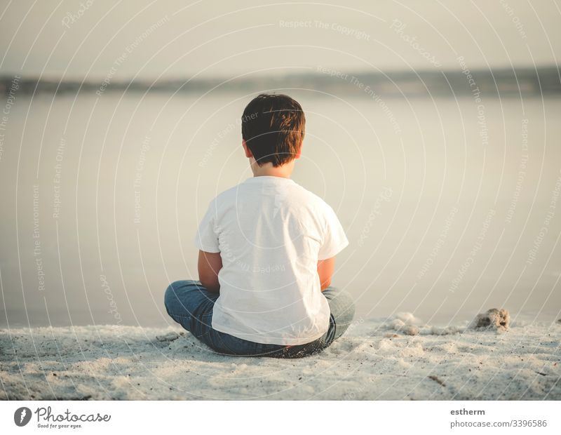 Back view of a Pensive child sitting on the beach childhood nostalgic thoughtful Thought loneliness lonely expression freedom innocence portrait serious dream