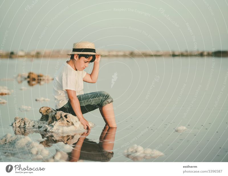 sad and pensive boy sitting on the beach child childhood nostalgic thoughtful Thought loneliness lonely expression freedom innocence portrait serious dream sea