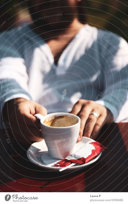 Man in white blouse holding a cup of coffee close up man hands cappuccino espresso beverages morning breakfast relax relaxation drink
