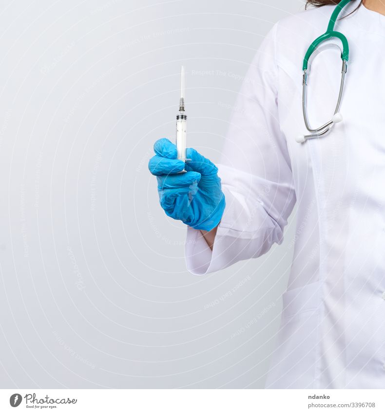medic woman in white coat and blue latex gloves holding a syringe, white studio background adult care caucasian clinic cure doctor dose drug equipment female