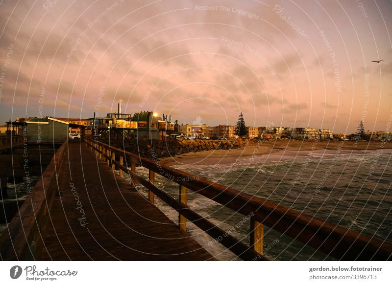 Harbour town in Namibia with landing stage in the foreground daylight Summer Panorama photo View from Landungsbrücke to the city few colours houses Factory
